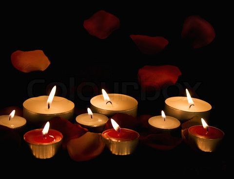 Image of 'Burning candles with petals roses on a dark background'