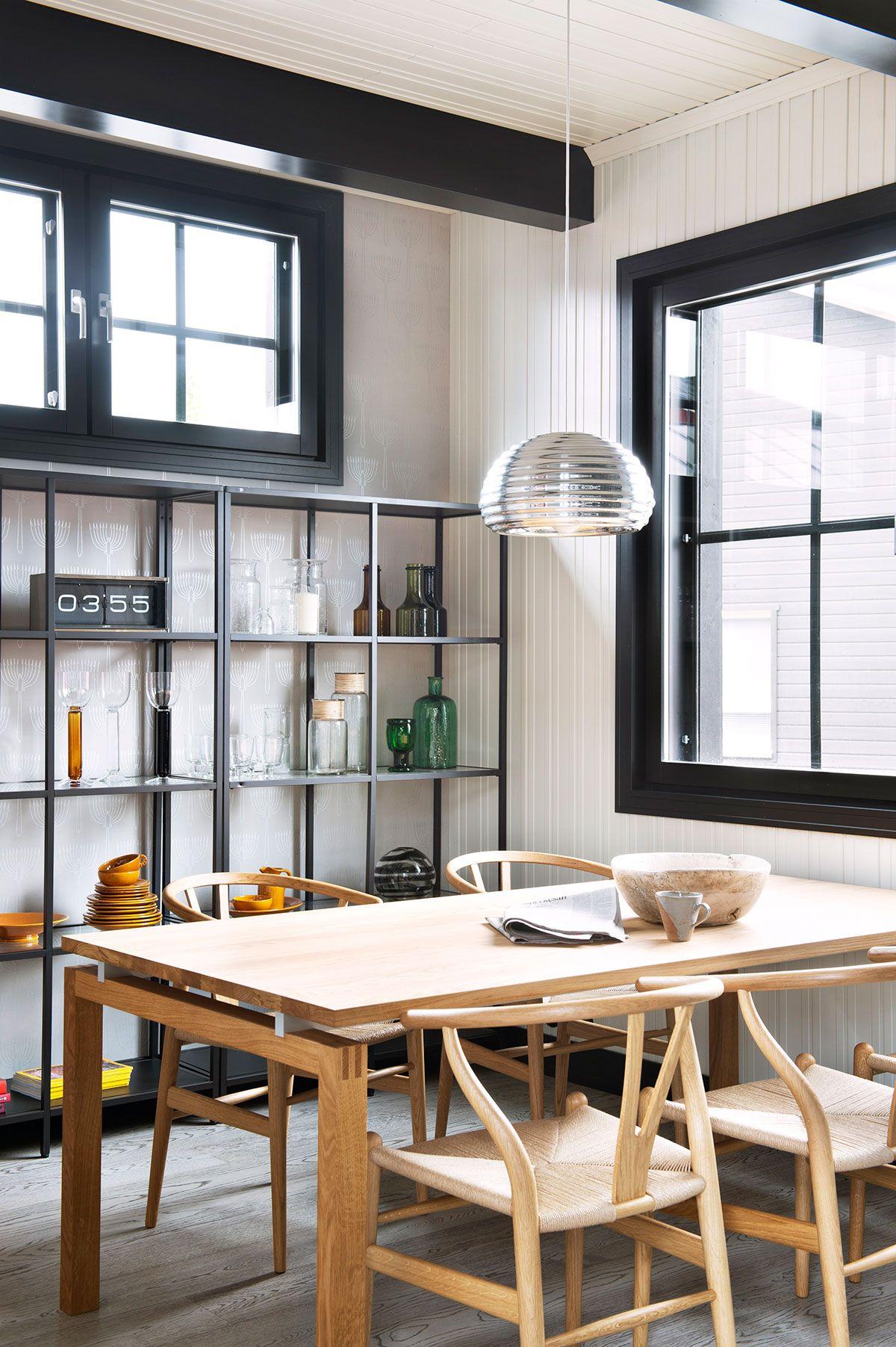 Musta hyllykkö toistaa mustapuitteisten Tiivin Kristalli-ikkunoiden ruudukkoa. Carl Hansenin SH700-pöytä ja CH24-tuolit ovat Nomartista. Pöydän yläpuolella on Flosin Splügen Bräu -riippuvalaisin.
