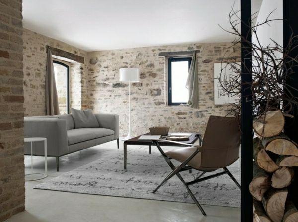 rustikales Wohnzimmer Natursteinwand graues Sofa Holz helle Farben