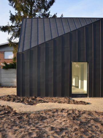 Une maison noire s\u0027immisce entre les arbres et la rivière Façade - Construire Une Maison De 200m2
