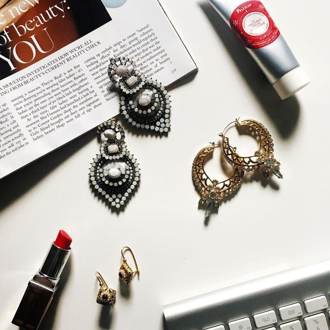 Flatlay with statement earrings and red lipstick