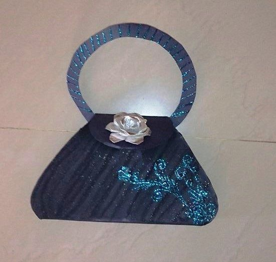 diy paper purse with glitter art and a paper rose on a top of it.