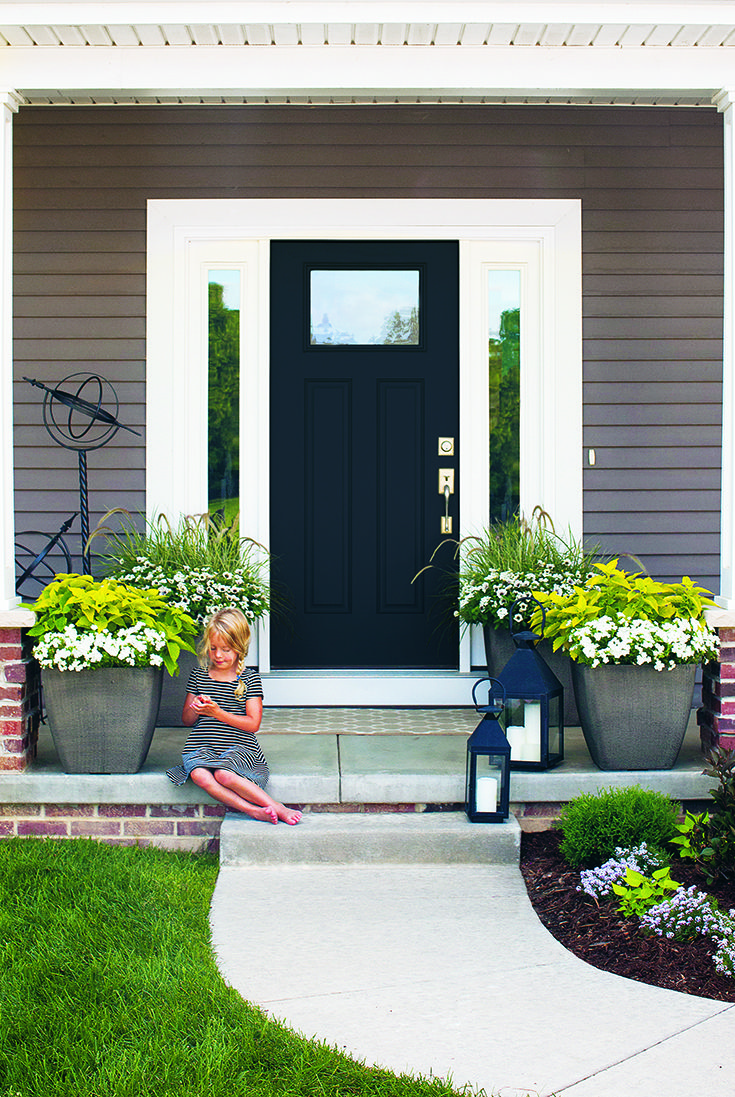 The Neutral Background With Gray Siding And A Black Door Set The