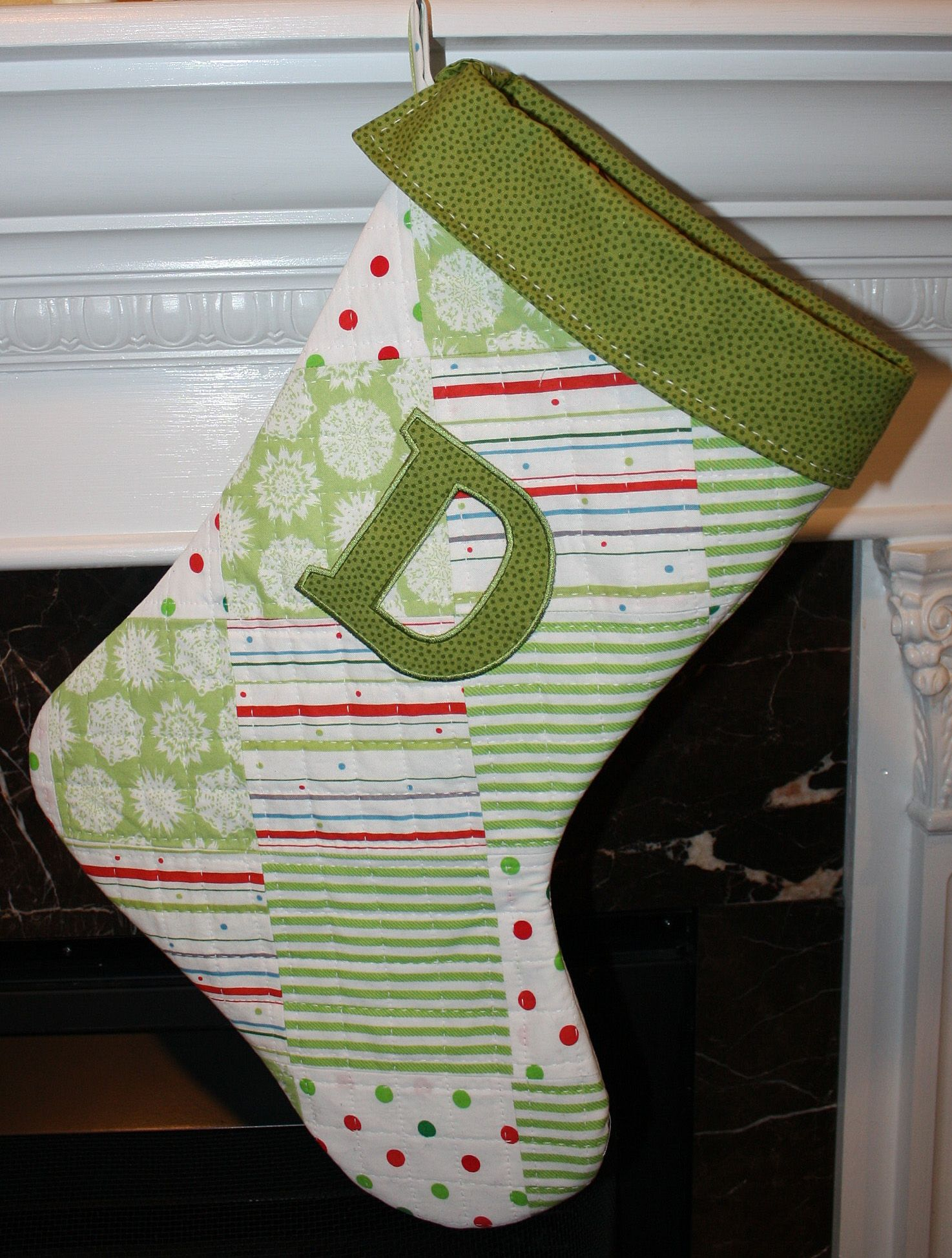 "A Sashiko quilted Christmas sock! Appliqued with a letter from ""Alphablock"" appliques. I made this by creating the pieced fabric first, then cutting out the stocking, applying the applique and finally quilting. That Sashiko stitch is so sweet!"
