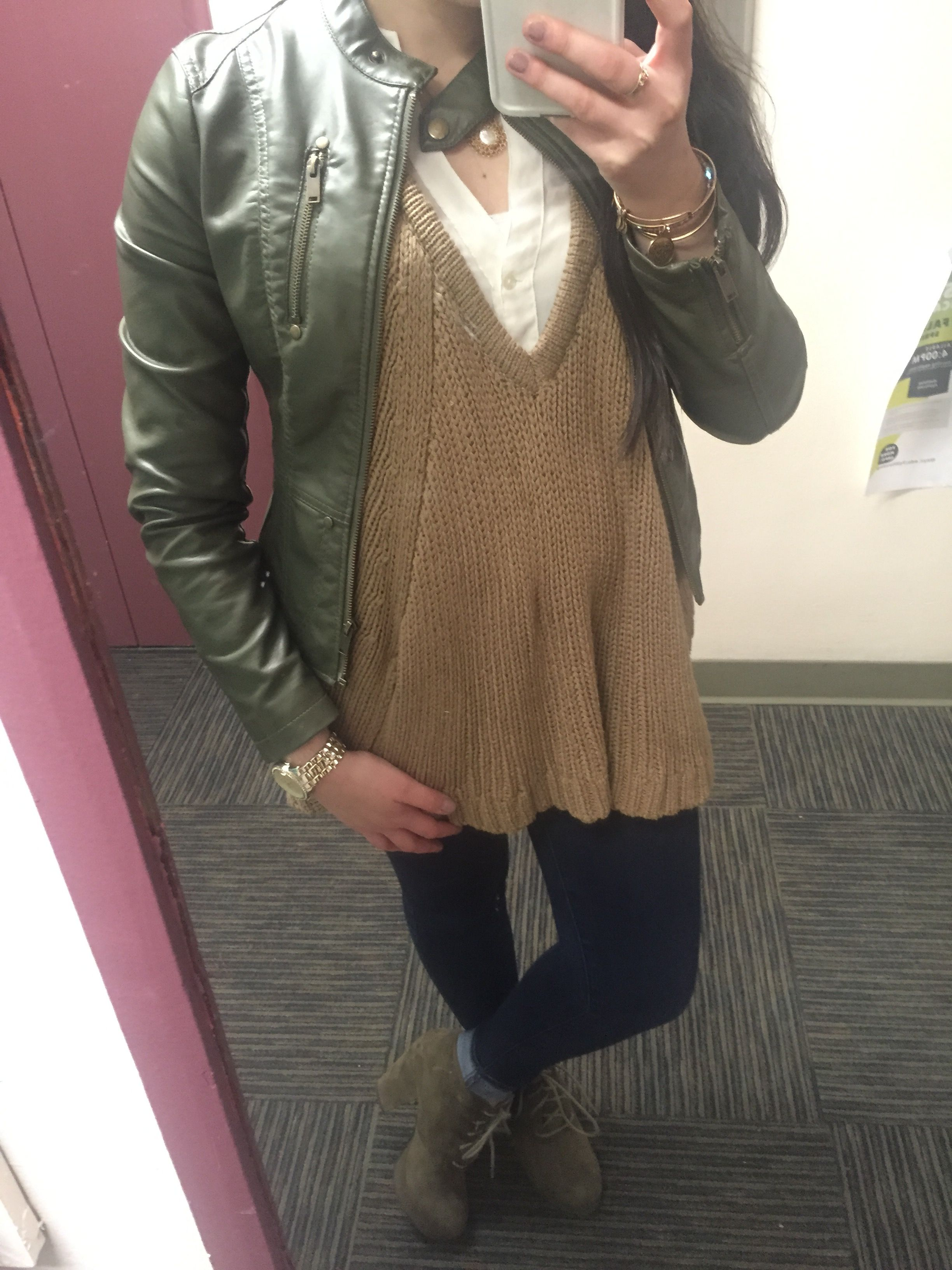 White button down with tan sweater and olive green leather jacket with dark jeans, olive green booties, and gold accessories