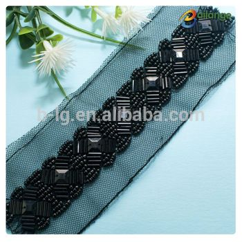 and rows of beads on black embroidered net with straps Beaded neck trim