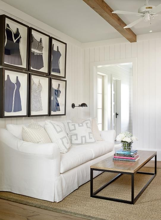 Framed blue and white vintage bathing suits are mounted to white vertical shiplap walls in a
