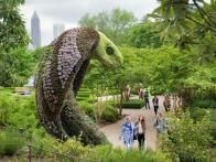"Set against the backdrop of downtown Atlanta, this gigantic cobra created by  Mosaiculture  towers over the visitors to the amazing ""Imaginary Worlds"" exhibit at the  Atlanta Botanical Garden ."