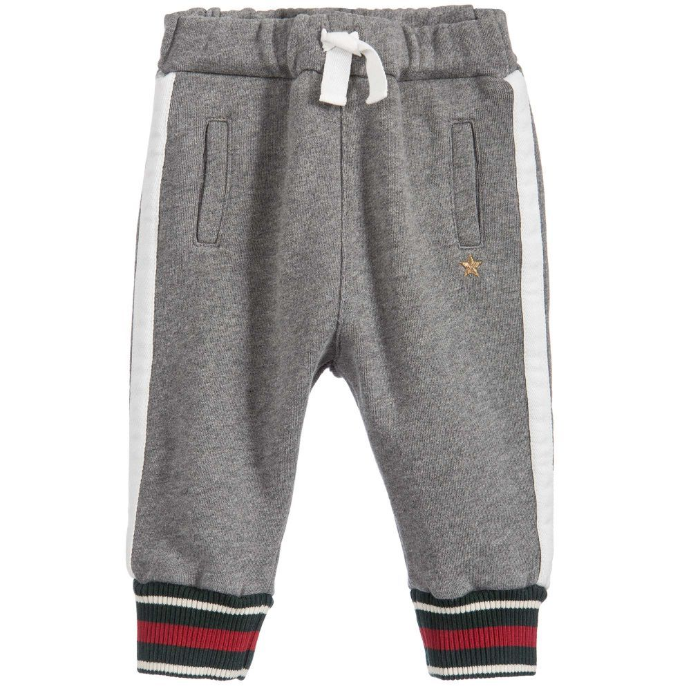 668608190f4 Baby boys grey Gucci tracksuit trousers featuring a gold embroidered star  and white appliqué stripes.