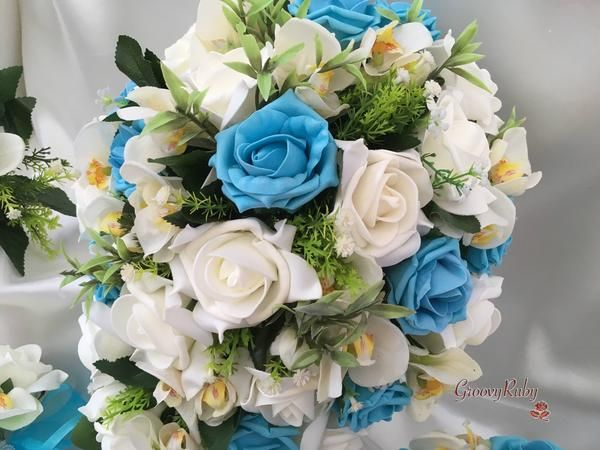 These beautiful, natural bouquets consist of realistic ivory orchids, roses and foliage. They are finished off with a colour co-ordinating satin ribbon handle w