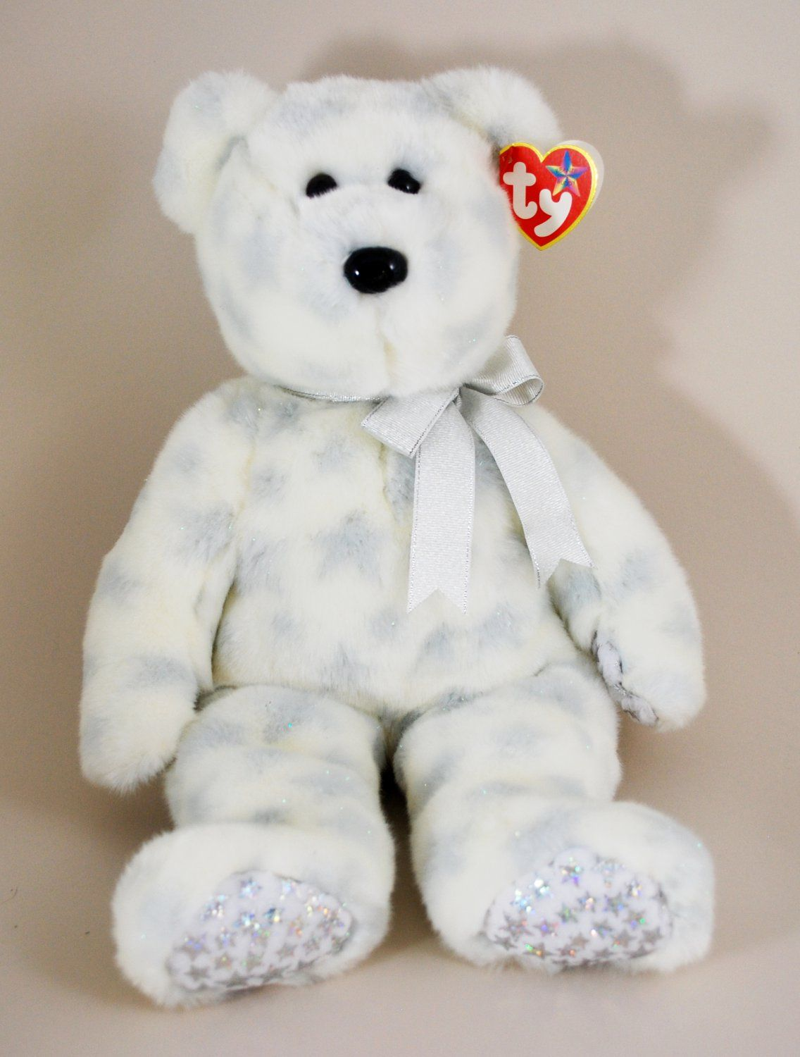 f8d5c3d6522 Ty The Beginning bear beanie buddy is a white and silver plush bear with  silver stars on his paw and feet pads. He has a silver ribbon around his  neck.
