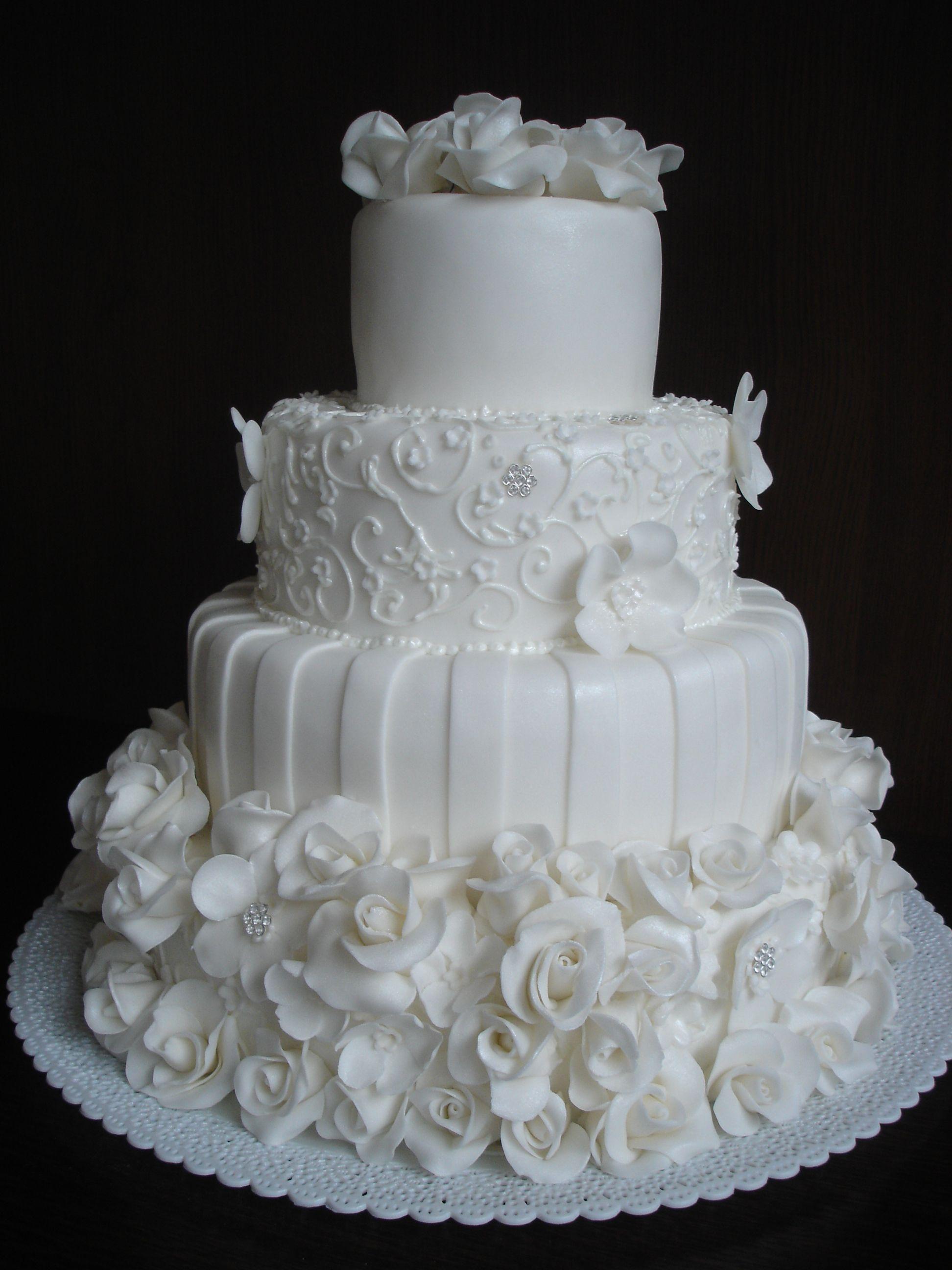f5f151e44 Něžná, romantická klasika je bílý svatební dort se spoustou růžiček,  bílkovým zdobením a třpytivým leskem fondánu.