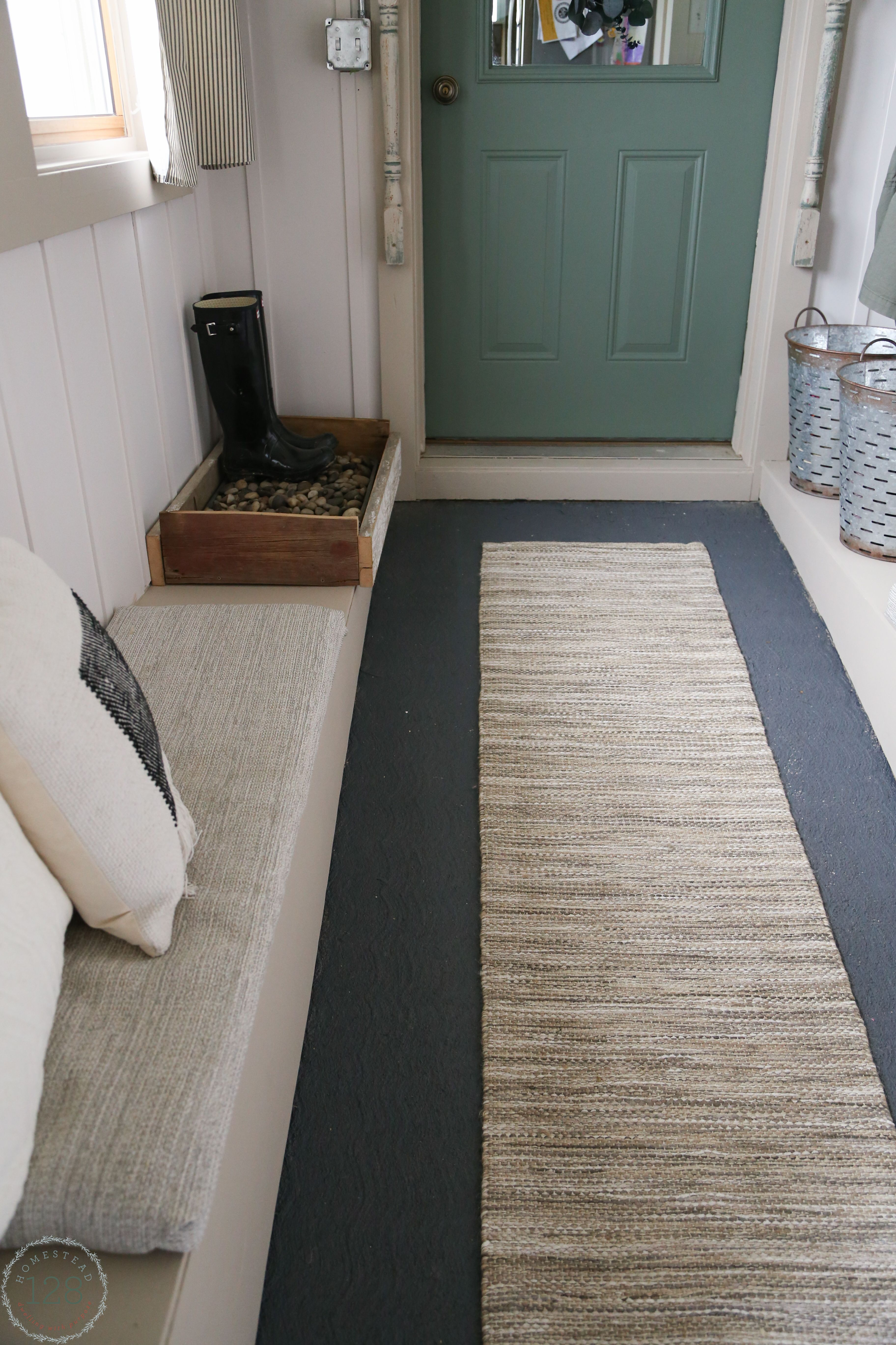 Gray painted cement flooring, upholstered benches, and shoe storage ...