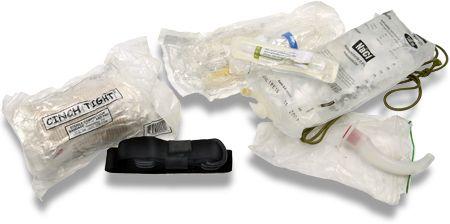 De grotere tas aan de chestrig bevat de trauma medickit voor de eerste levensreddende handelingen. Links een drukverband en een tourniquet om zelf ernstige (slagaderlijke) bloedingen te kunnen stelpen. Rechts een gebogen buisje om in de keel de luchtweg te kunnen openleggen (een zogenaamde mayotube) en een compleet draagbaar infuus om vocht toe te kunnen dienen.