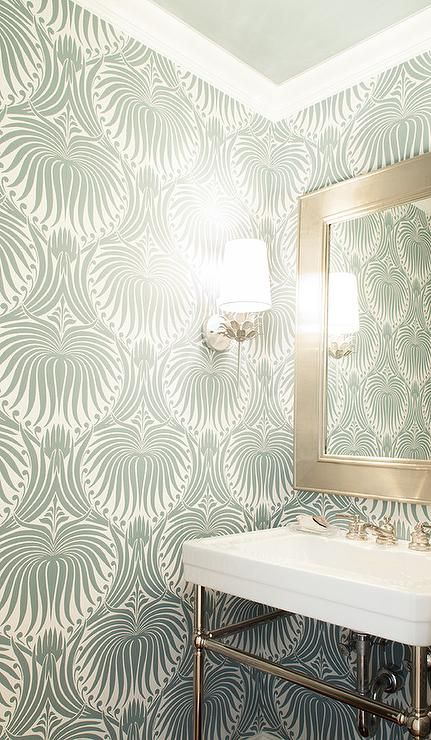 Chic powder room features walls clad in green wallpaper, Farrow & Ball Lotus Wallpaper, lined with a 2 leg washstand and a silver beveled mirror illuminated by a Worlds Away Delilah Silver Wall Sconce.