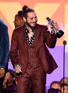Post Malone at the 2018 VMA awards shows a more masculine take on dandy style, pairing a three piece suit made from dark and striped fabric with a black polka dot shirt that has been unbuttoned to the vest. #postmalonewallpaper Post Malone at the 2018 VMA awards shows a more masculine take on dandy style, pairing a three piece suit made from dark and striped fabric with a black polka dot shirt that has been unbuttoned to the vest. #postmalonewallpaper