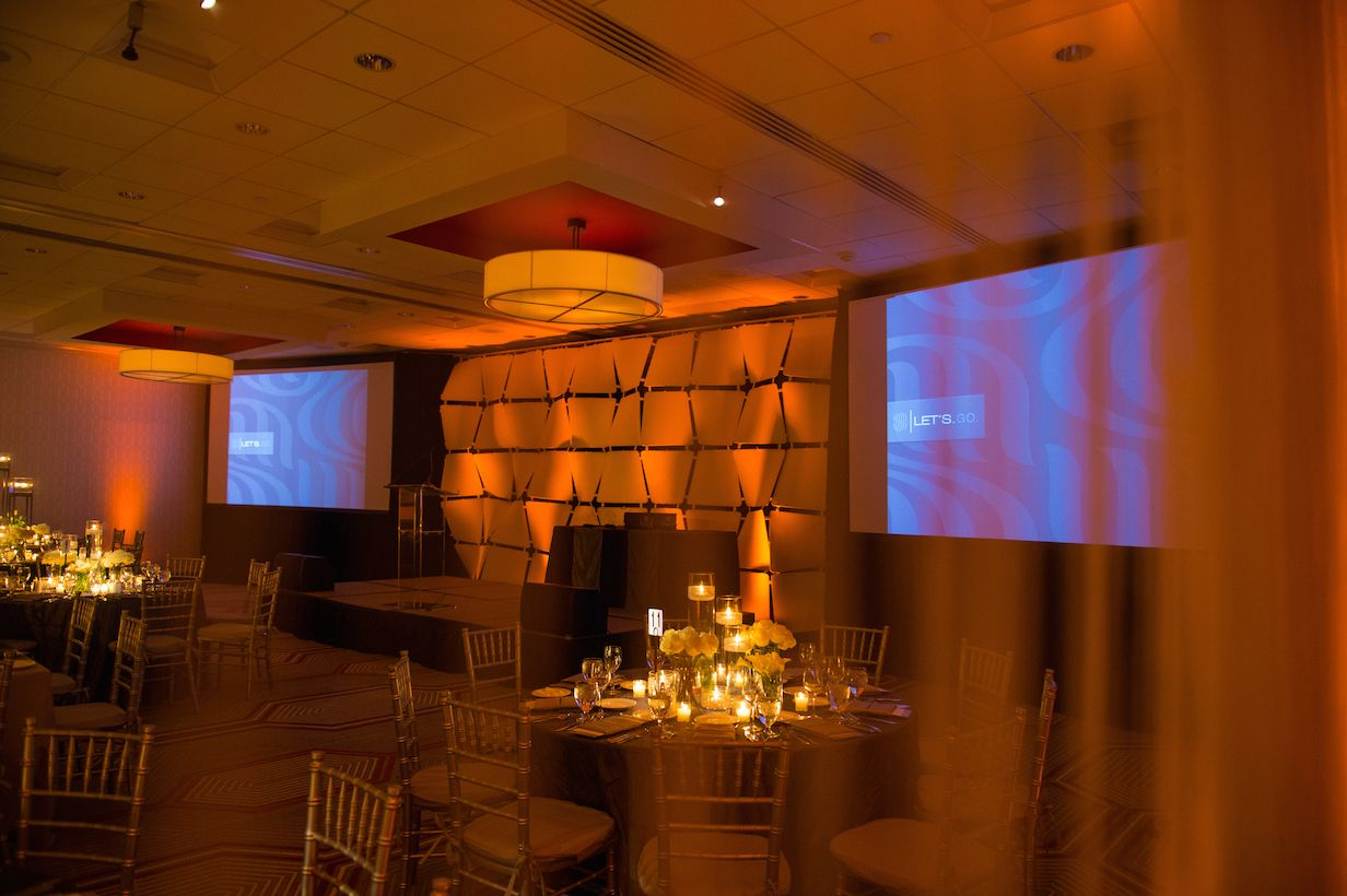 LED uplighting, pin spotting, stage wash, wafer wall backdrop, lucite podium, projectors & screens, and PA system for a corporate gala. Audio/visual production & lighting by Synergetic Sound + Lighting. Photo by Joey Bleiler of The Wise Image. http://blog.synergeticsounds.com/2015/02/19/corporate-delivering-the-message/