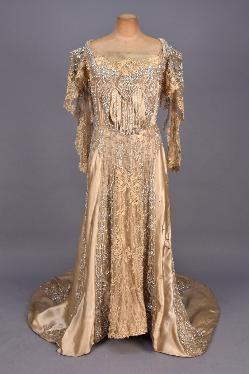 BEADED SILK and LACE GOWN with TRAIN, 1905 - 1907. Ivory satin lavishly decorated with nacreous beadwork and applique lace on net, boned bodice having long, open lace sleeve, rounded train. Unlabeled. B-40, W-28, front L-54, back L-74. (Silk lining shattered, allover splits to satin, scattered holes to net, some bead losses) for study use or salvage only, fair. MCNY