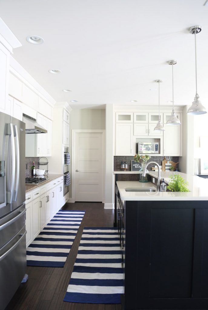 White kitchen cabinets with black island and navy striped rug via Life On Virginia Street