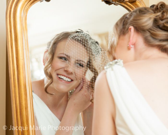 Bride Putting On Her Earrings In The Mirror Photographed By Hampshire Wedding Photographers Jacqui Marie