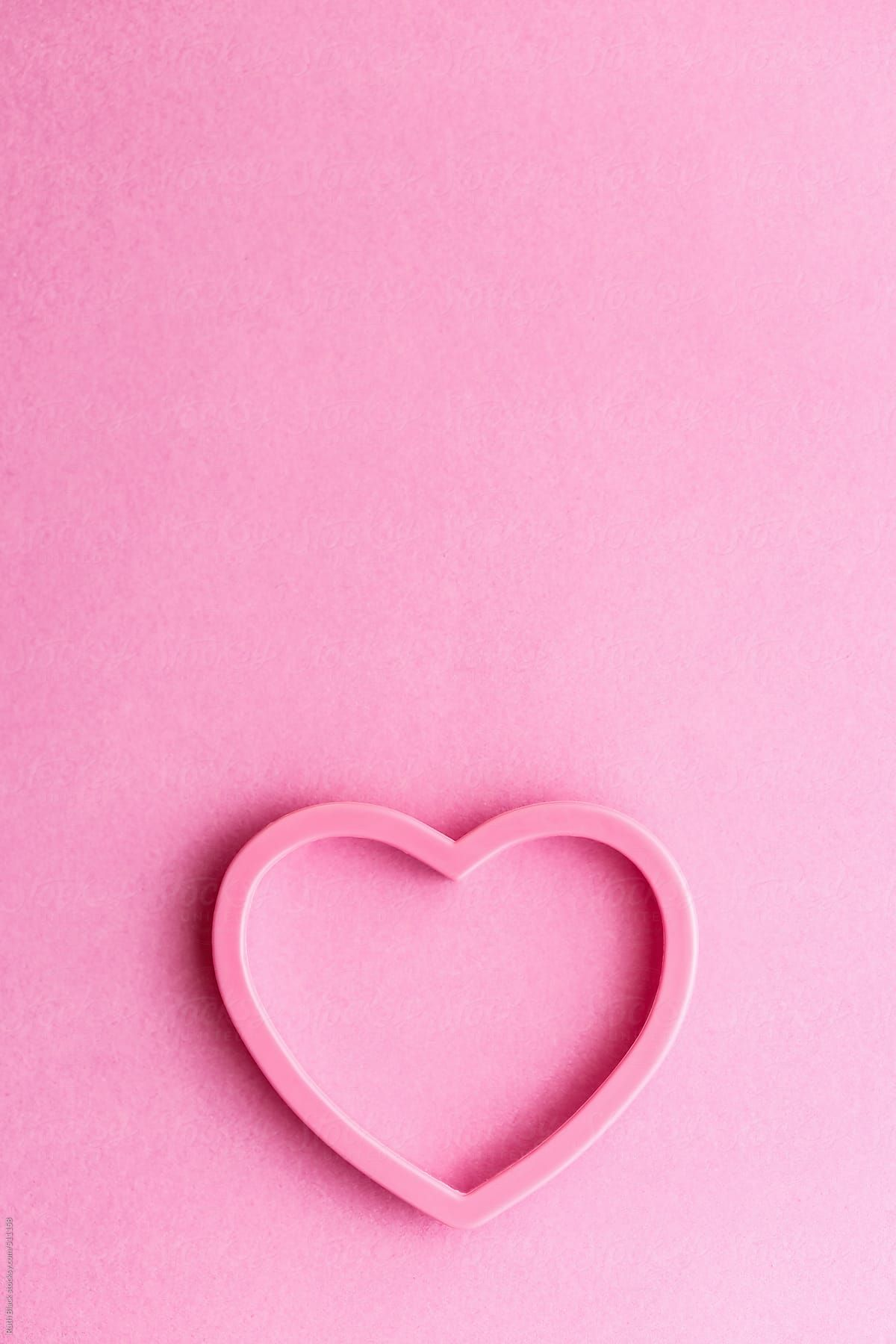 Heart shaped cookie cutter on pink by Ruth Black for Stocksy United