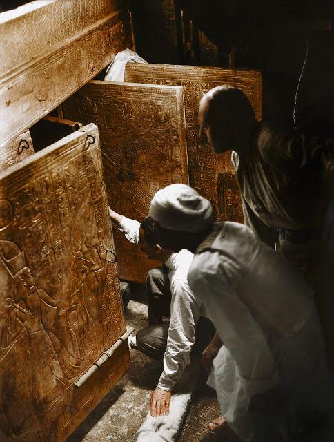 The Discovery of Tutankhamun in the 1920s in Color - 4th January 1923, Tutankhamun's Tomb | Howard Carter (kneeling), Arthur Callender and an Egyptian workman in the Burial Chamber, looking through the open doors of the four gilded shrines towards the quartzite sarcophagus.