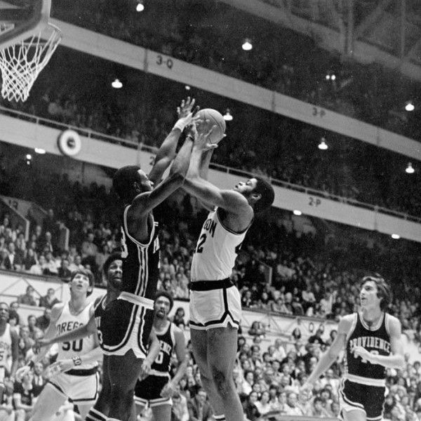 Black and white photo of University of Oregon basketball player Greg Ballard going up for a shot against Providence in a game played on January 4, 1975 at McArthur Court, while Gerald Willett (#50) gets into rebounding position and Ernie Kent (far left) watches from the corner. The Ducks won the game 86-73.