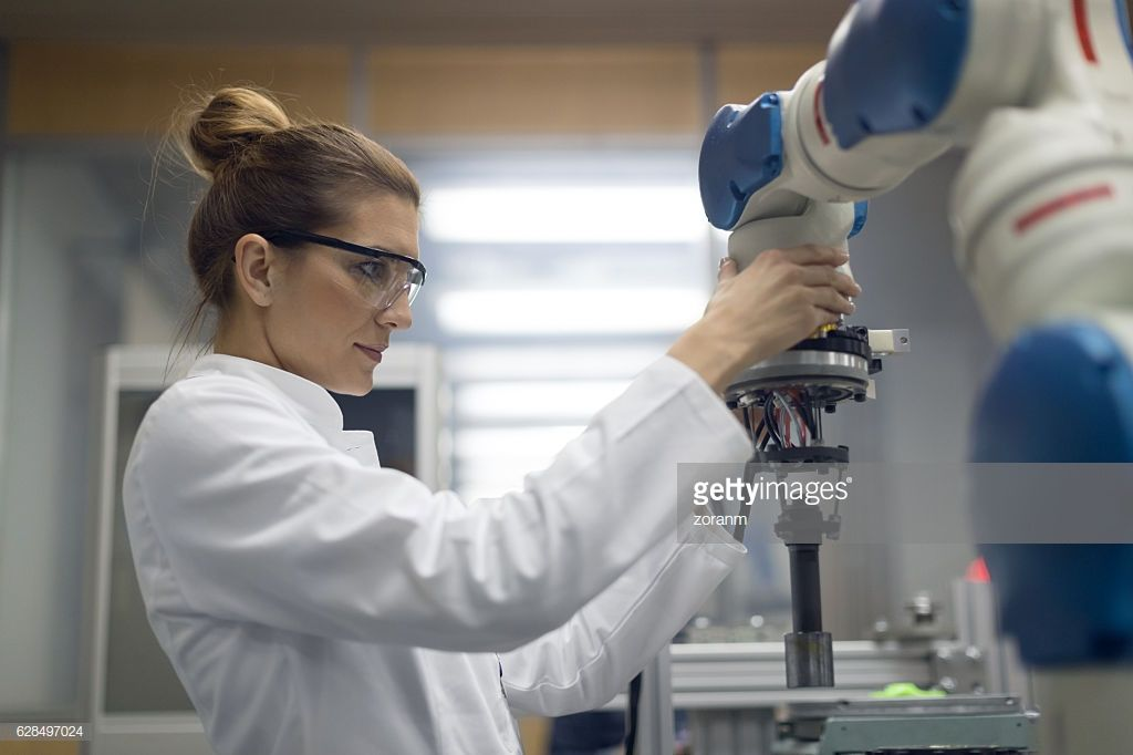 Mid adult female electrical engineer working with robotic