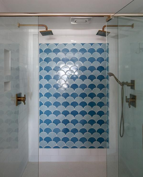 Behind a glass enclosure finished with brass hardware, this stunning walk-in shower features facing square brass rain shower heads and a brass sprayer mounted on white brick wall tiles facing a tiled shower niche while the center wall is accented with blue fan pattern shower accent tiles.