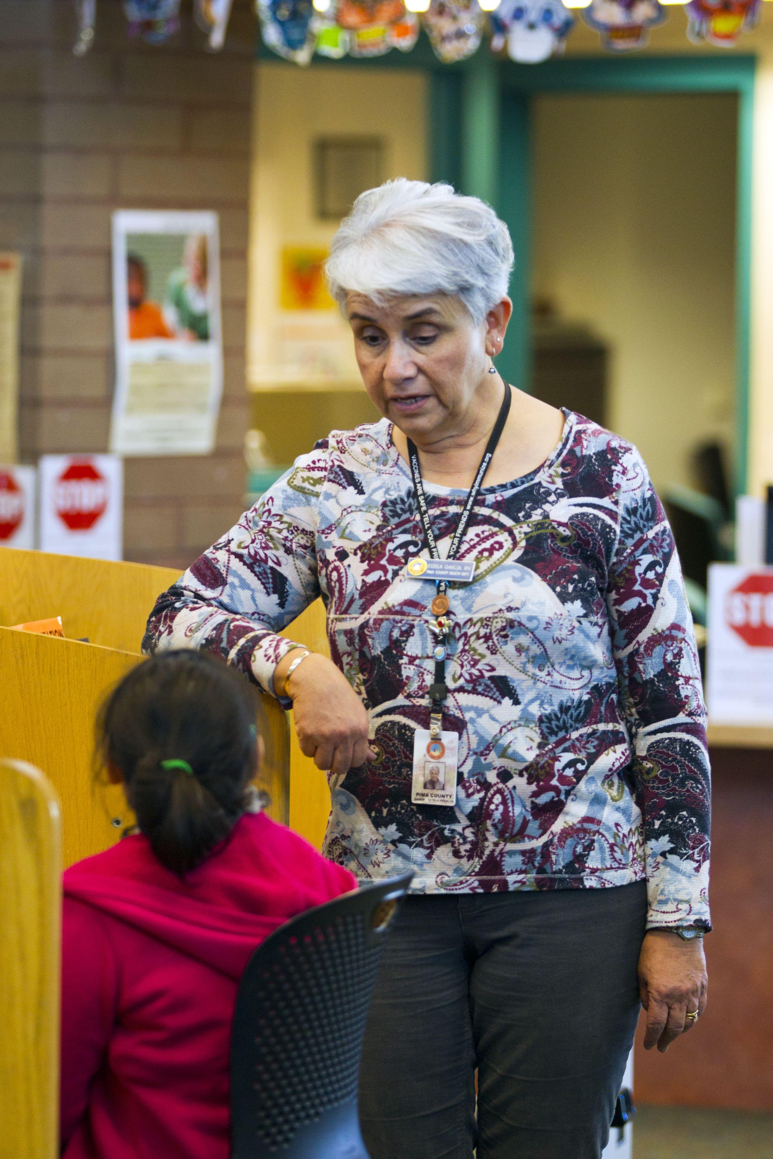 Pima County Public Library Nurse Estela Garcia talks with