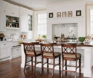 White kitchen with wood bar stools and wood island counter top