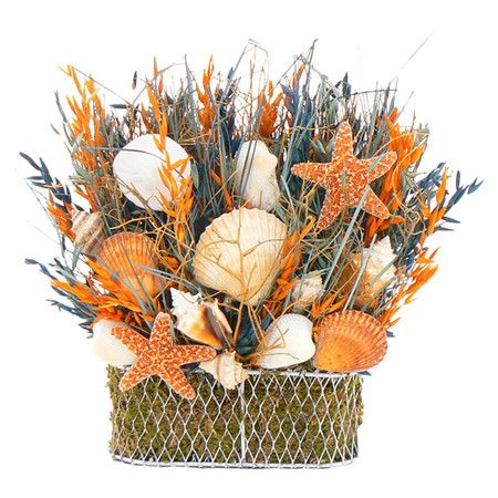 Assorted dried grass and seashell arrangement in woven wire basket.  Product: Floral arrangementConstruction Material: