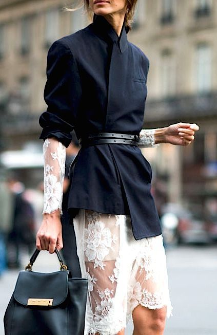Belted navy coat over a white lace dress with long sleeves.