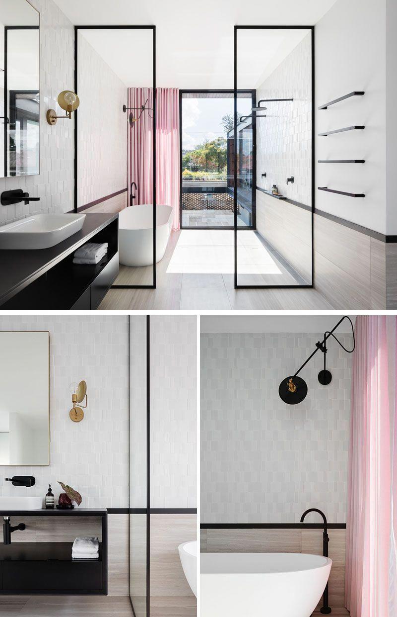 In the master bathroom, black-framed glass shower screens ...