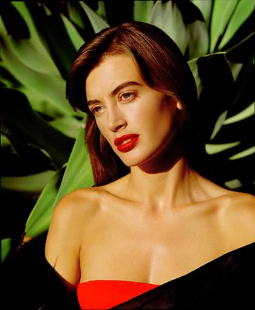 late afternoon sunlit photo of Amanda Pays in Donna Karan red strapless dress with black off the shoulder cape standing in front of lush dee...