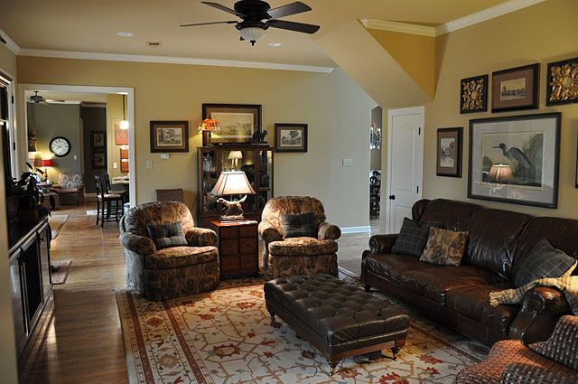 A brown leather sofa in room with vanilla y walls and wood for Rug for brown couch