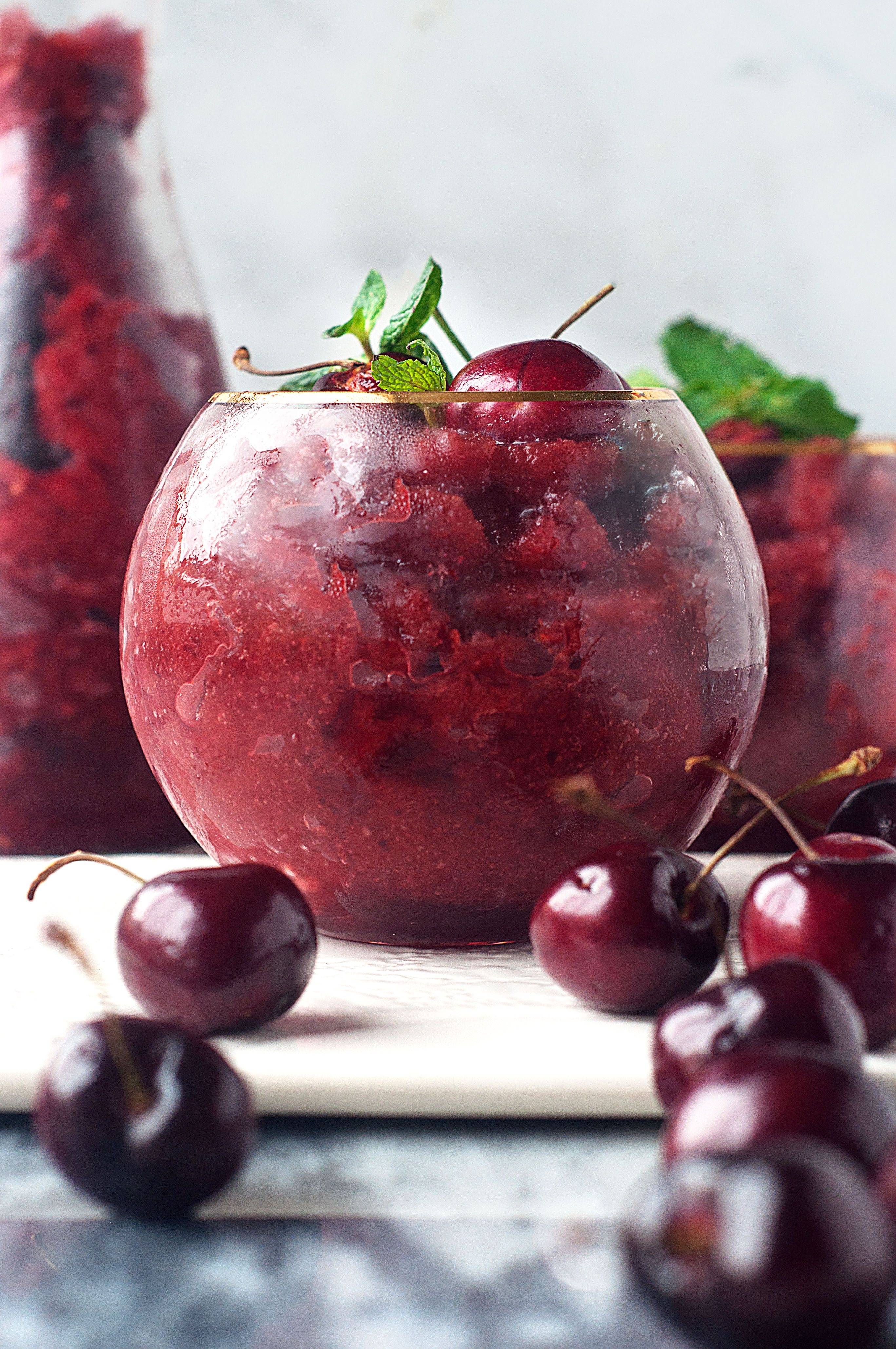 Frozen cherries blended with ginger beer, honey, lime and vodka for a refreshing summer slushie cocktail!