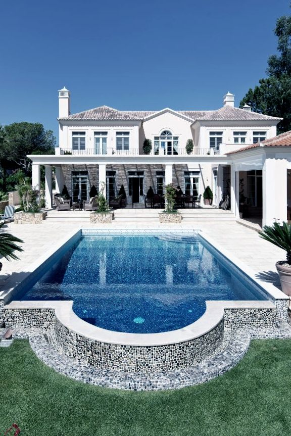 Traditional shaped pool with a tiled wall and blue for Pool design hamptons