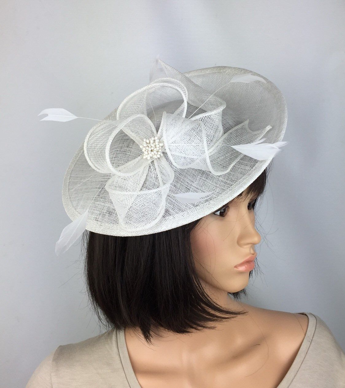 White Fascinator Wedding White Hatinator Ladies Day Races Mother of the Bride Occasion Hair Fascinator #fascinatorstyles A Pretty Elegant white hair fascinator / hatinator to compliment your stylish outfit. Perfect to wear at a wedding whilst being a beautiful mother of the bride or guest, make a statement at the races or for a memorable occasion where you want to stand out from the crowd. • This striking saucer / disc style hatinator has been made from quality sinamay. The focal point of the #fascinatorstyles