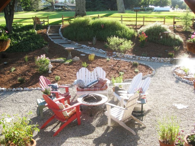 A Gravel Patio Features Adirondack Chairs And A Fire Pit. Cute!