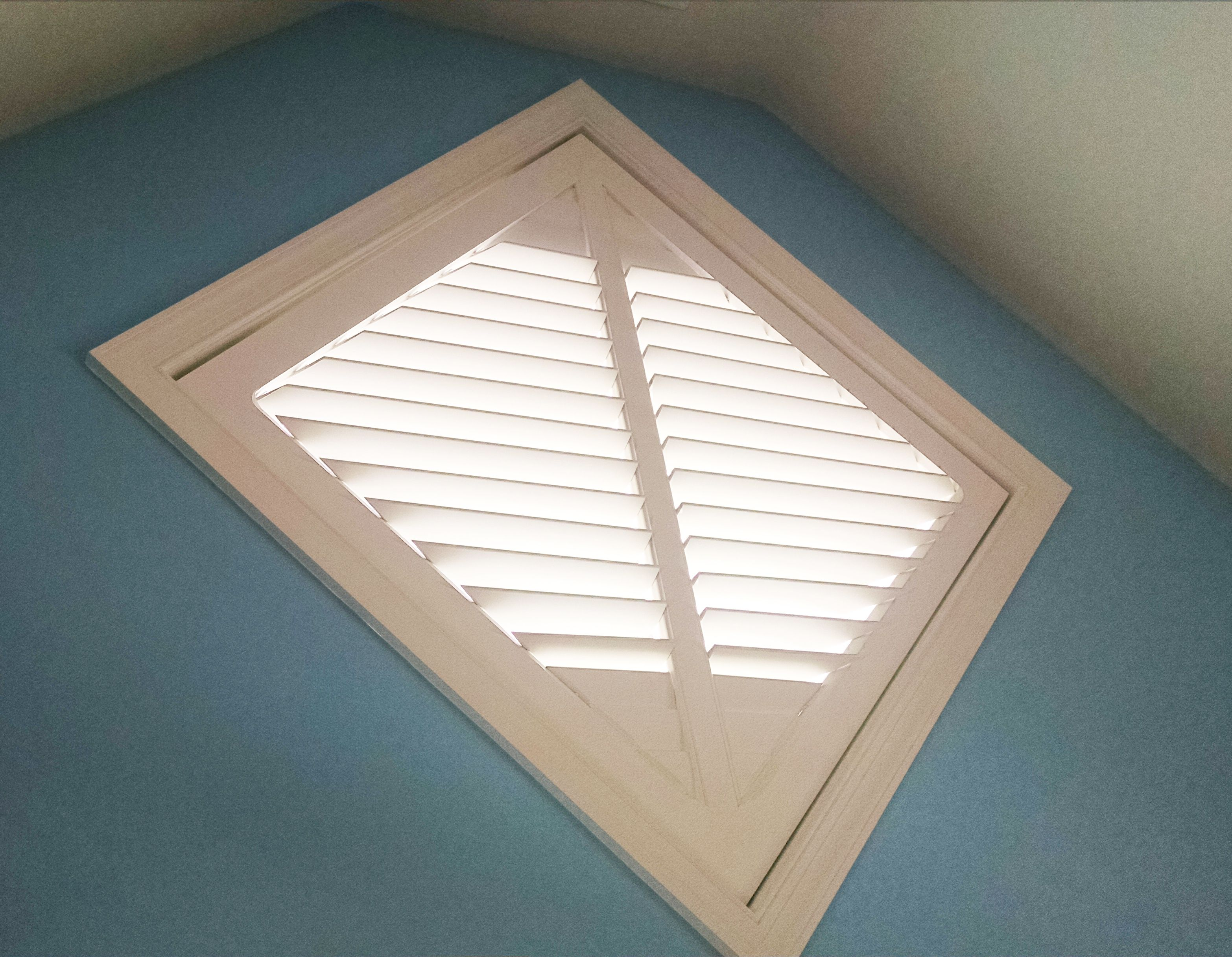 Diamond Shaped Window Covered With Plantation Shutters By