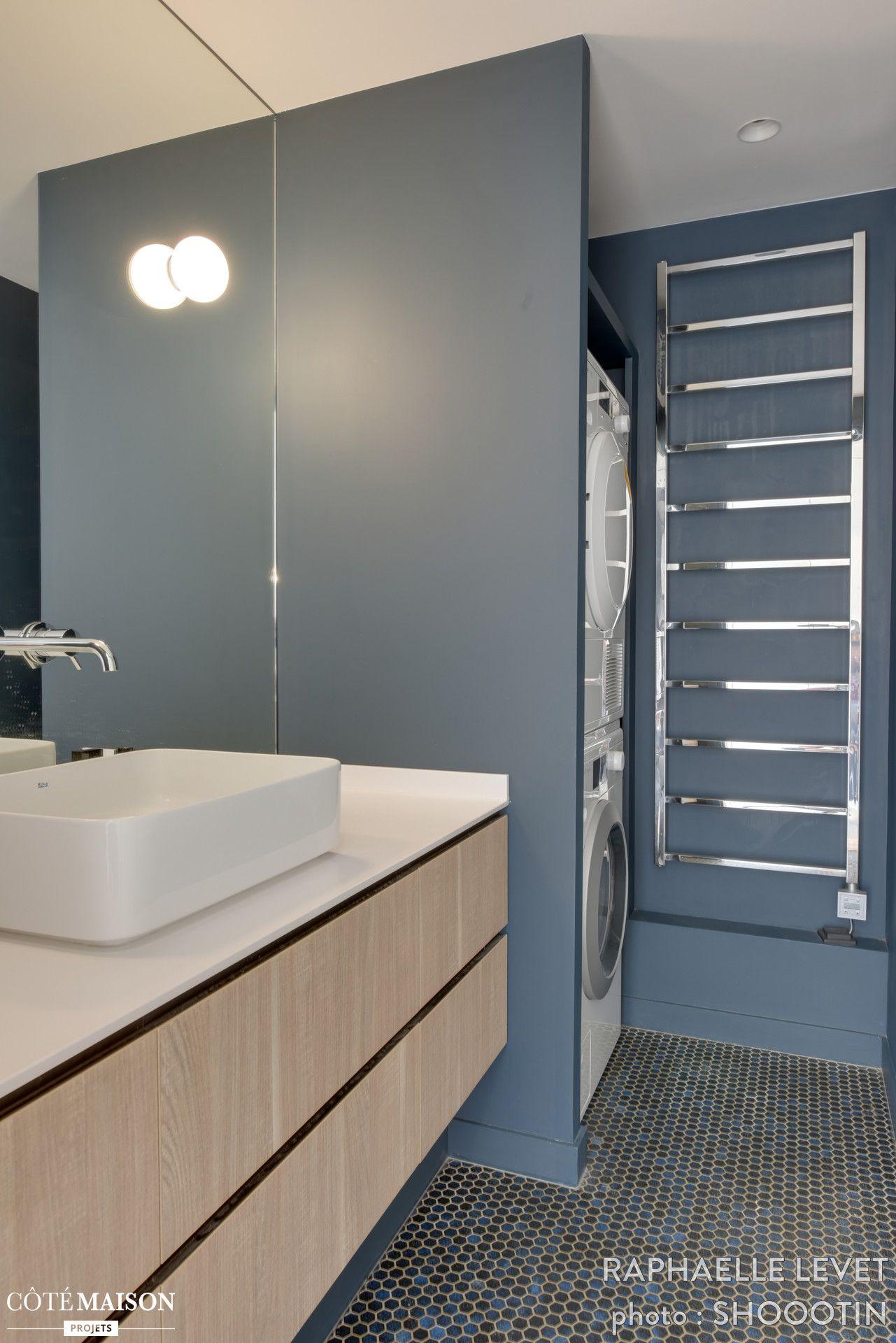 Cette élégante salle de bains partage son espace avec la buanderie ...