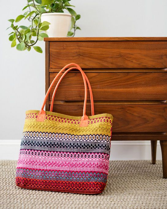 Travel anywhere with this bohemian woven cotton tote bag. With its bright mix of golds, reds, and jewel tones, sassy bright orange leather handles, and plenty of room to hold all your necessities, this tote is the perfect, practical accessory both on the road and at home.