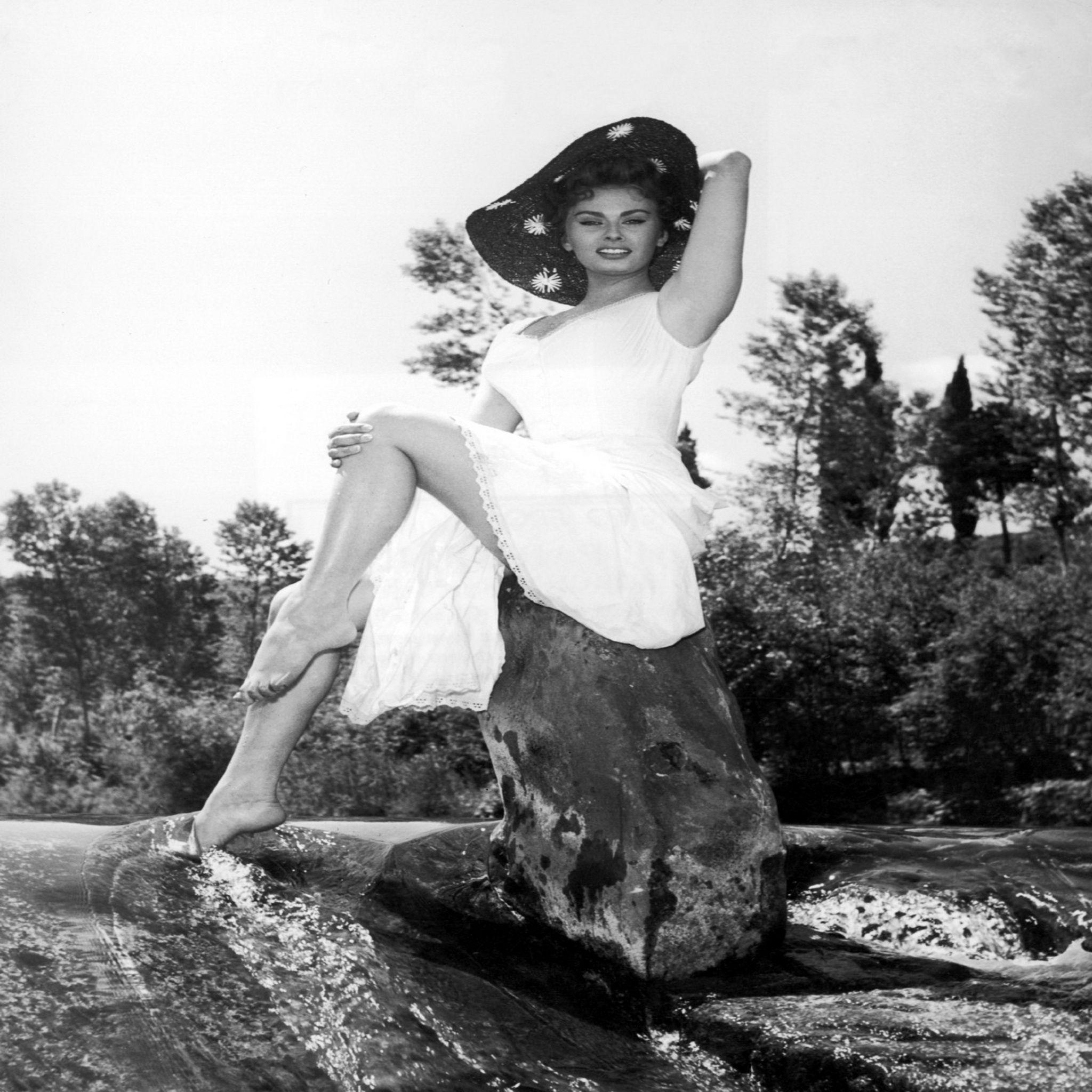 1955: Italian actor Sophia Loren poses barefoot on a rock in a ...