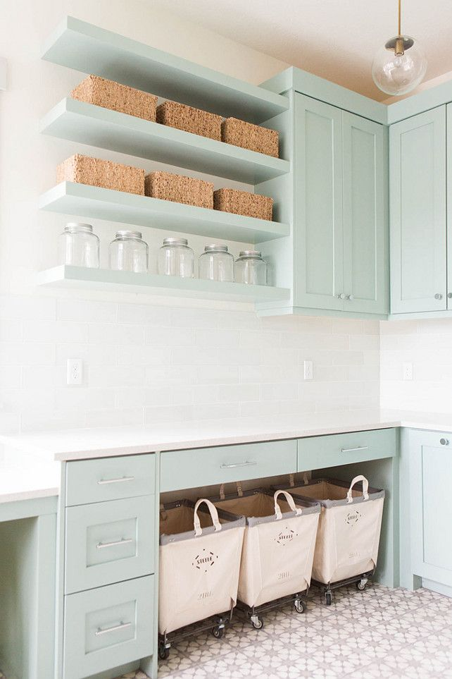 Laundry Room Design. Laundry room features gray green cabinets paired with…