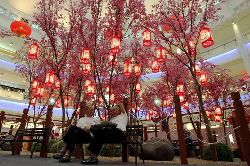 Two men infront of plum blossom tree decorations in Kuala Lumpur, Malaysia