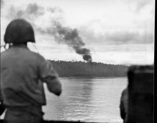 Smoke billows from the shells of the U.S. Navy destroyers Wilkes and Nicholson, providing close fire support for the American infantrymen fighting the Japanese onshore at Biak. This photo was taken on May 27, 1944, the day the U.S. troops landed on the island in the Schouten group near the western tip of New Guinea.