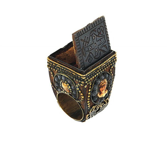 A 19th century 'Papal' ring   The large ring with square bezel mounted with a hinged iron panel revealing a velvet lined compartment, the panel engraved with the arms of the Piccolomini family, the broad tapering shoulders and sides decorated with an oval coral corallium rubrum cameo depicting a classical female head within a cut steal border and applied ribbon and V shaped motif with beaded detail, Italian, circa 1830