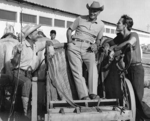BEN HUR - Horse trainer Glenn Randall, stunt coordinator Yakima Canutt (standing in chariot) & Charlton Heston on the set in Rome.