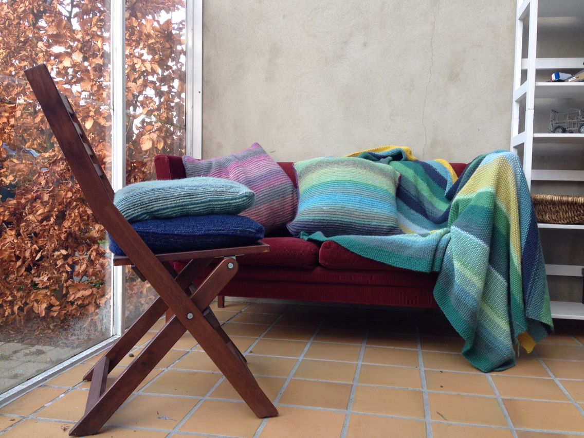 Strikkede puder og tæppe. Ren uld, blå og grønne farver, havestuen er meget mere fristende.
